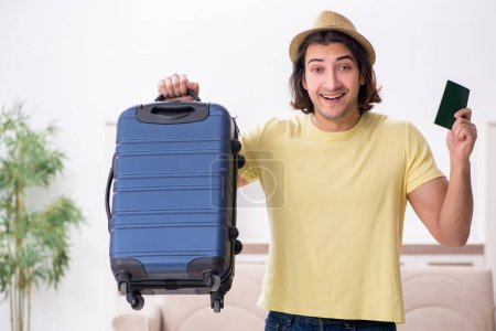 Photo for Young man holding passport and suitcase preparing for the trip - Royalty Free Image