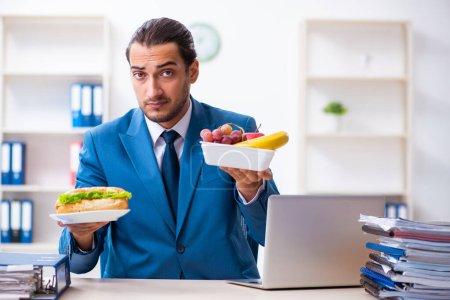 Photo pour Jeune employé petit déjeuner sur le lieu de travail - image libre de droit