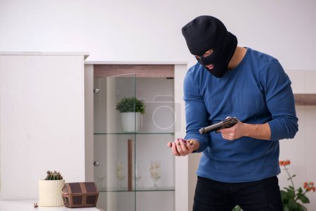 Photo pour Un voleur vole des objets de valeur à la maison - image libre de droit