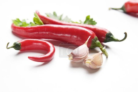 Food composition of red chilli peppers, garlic and parsley isolated on white background