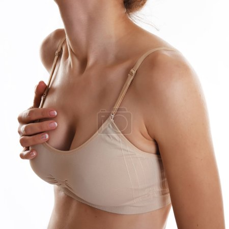 Mid section view of woman in beige top touching breast feeling pain