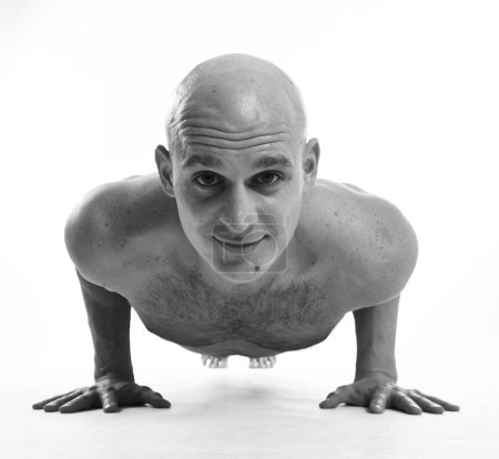 Black and white view of bald man doing push-ups