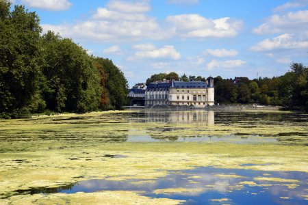 Chateau de Rambouillet castle near river on background of blue sky and white clouds, France.