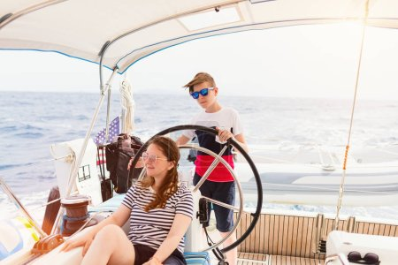 Family of mother and son on board of sailing yacht having summer travel adventure