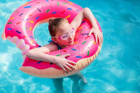 Adorable girl with pink inflatable ring swimming in a pool on summer vacation