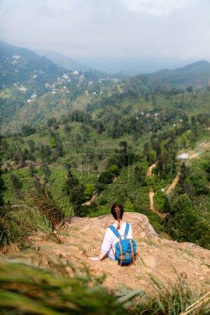 Young woman enjoying breathtaking views over mountains and tea plantations from Little Adams peak in Ella Sri Lanka