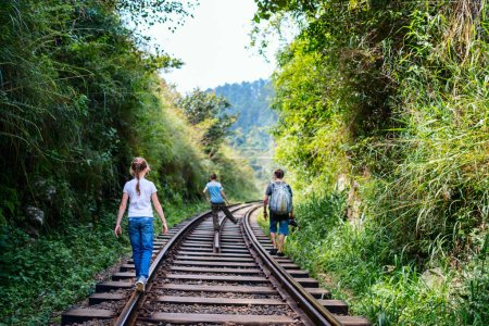Family of father and two kids walking along train tracks in Sri Lanka