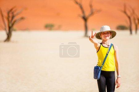Photo pour Adorable jeune fille parmi les camélidés morts entourés de dunes rouges à Deadvlei en Namibie - image libre de droit