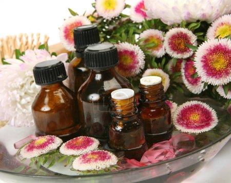 Photo pour Fleurs et des bouteilles d'huile aromatique dans un bol avec de l'eau - image libre de droit