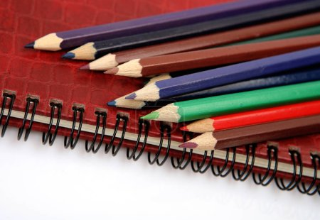 Photo for Colored pencils for drawing and notebook on a white background - Royalty Free Image