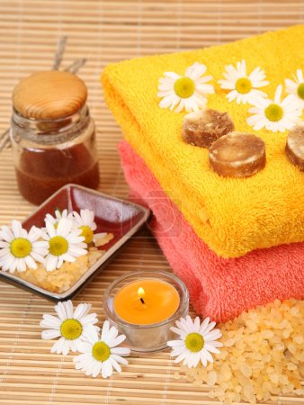 colored towel, body care items and burning candles