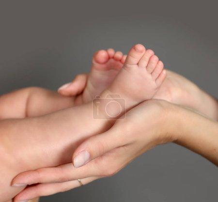 Die Hände der Mutter halten den Fuß des Kindes