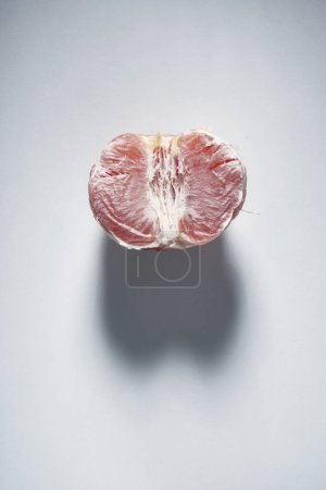 Foto de Analogy, a sexual grapefruit in the form of a female vagina, with a shadow in the form of male eggs on a gray background - Imagen libre de derechos