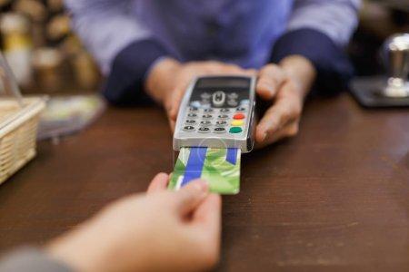 Photo pour Photo de l'acheteur avec carte bancaire et le vendeur avec le terminal en main au magasin - image libre de droit