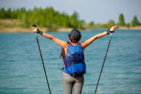 Image of back of sporty woman with walking sticks and backpack on lake background