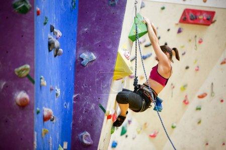Photo pour Photo de fille de sport avec talc sac derrière son dos pratiquant sur le mur d'escalade dans la salle de gym . - image libre de droit