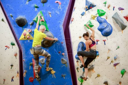 Photo for Photo of two sports women compete on wall for rock climbing indoors - Royalty Free Image