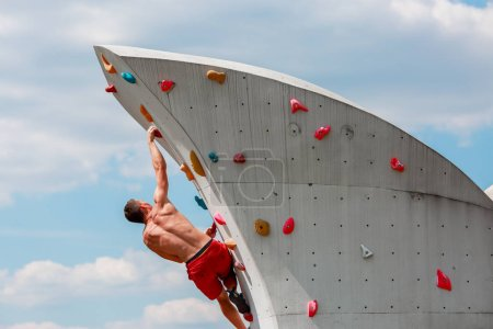 Photo from back of young sporty man in red shorts hanging on wall for rock climbing against blue sky with clouds