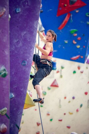 Photo for Photo of young girl exercising on climbing wall in gym - Royalty Free Image