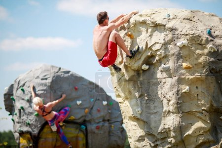Photo from back of young athlete guy in red shorts and woman on workout at climbing boulders against blue sky with clouds