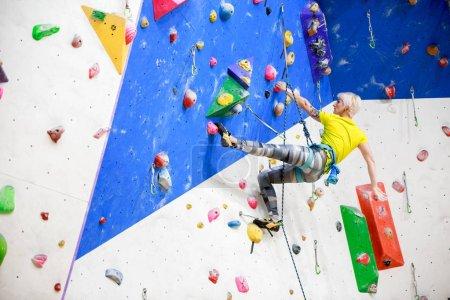 Photo pour Photo de dos de fille sportive en vêtements de sport brouille sur le mur pour l'escalade à l'entraînement dans la salle de gym - image libre de droit
