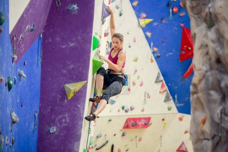 Photo for Photo of young athlete woman looking down climbing up purple wall indoors - Royalty Free Image
