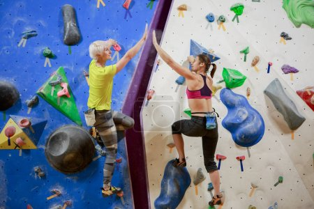 Photo of two woman athletes making handshake on climbing wall in sports hall