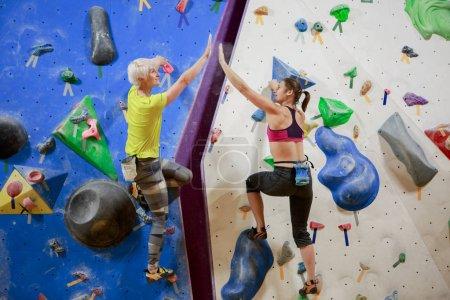 Photo pour Photo de deux athlètes féminines serrant la main sur un mur d'escalade dans une salle de sport - image libre de droit
