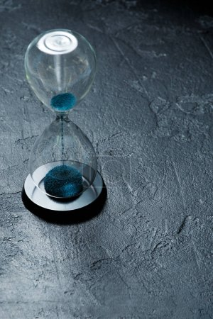 Photo for Photo of hourglass with blue sand on black stone background, space for text - Royalty Free Image