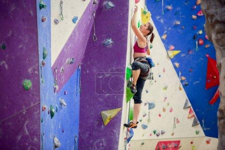 Photo pour Photo de jeune athlète femme regardant vers le haut escalade mur violet à l'intérieur - image libre de droit