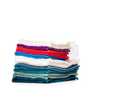 Photo of stacks multi-colored towels on empty white background.