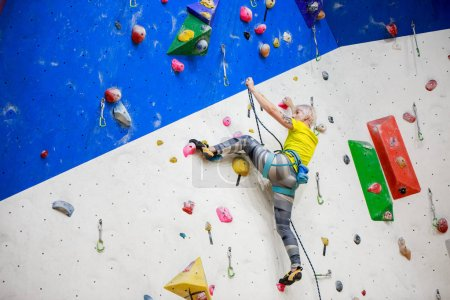 Photo from back of young sportswoman in yellow T-shirt scrambles on wall for climbing at workout