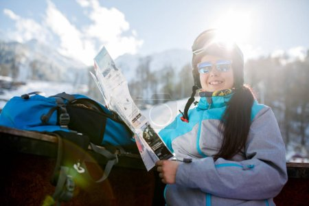 Photo of smiling woman tourist in helmet with map in hands on background of mountains