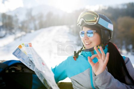 Photo of smiling female tourist in helmet with map in hands on background of mountains