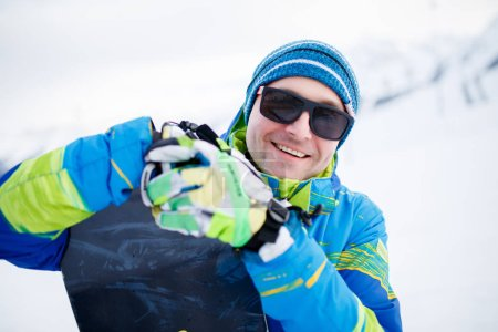 Portrait of smiling man in sunglasses with snowboard in hands on background of snowy mountains