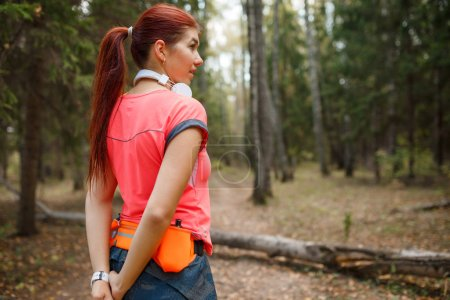 Photo for Image from back of young sportswoman standing in forest on summer day - Royalty Free Image