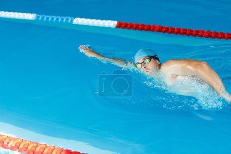 Photo of side of sports man in blue cap swimming under water in pool at training room
