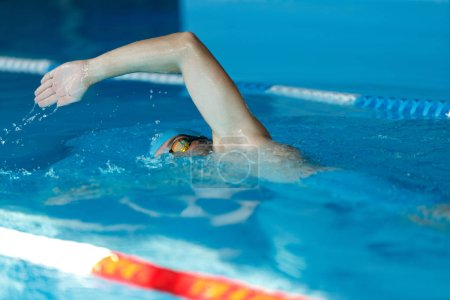 Side view of young sports man in blue cap floating on path in pool