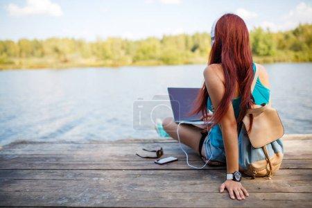 Photo pour Image sur l'arrière de la brune dans les écouteurs avec sac à dos et portable en mains, assis sur la rive du fleuve en après-midi d'été - image libre de droit