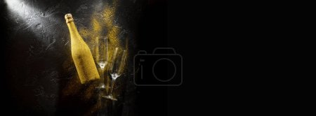 Photo for Image of golden champagne bottle, two wine glasses on black stone background, empty space for text - Royalty Free Image