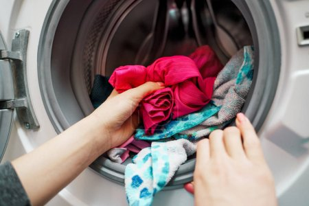 Photo for Image of female hands putting dirty clothes in washing machine in apartment - Royalty Free Image