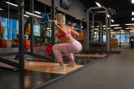 Photo pour Photo de l'arrière de la jeune fille blonde accroupie avec haltères sur ses épaules dans une salle de sport au cours de la formation - image libre de droit