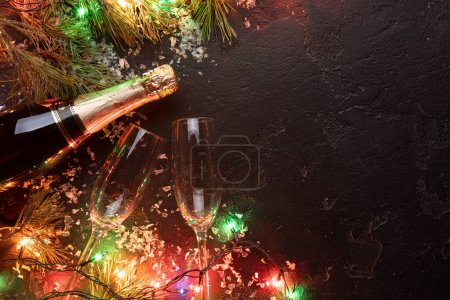 Photo for Photo on top of branches of spruce, burning garlands, bottle of champagne, two wine glasses on empty black background, place for text. - Royalty Free Image
