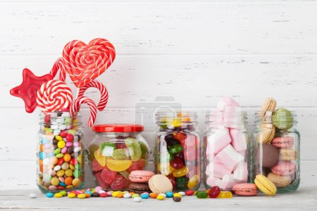 Colorful sweets. Lollipops, macaroons, marshmallow, marmalade and candies. With space for your greetings