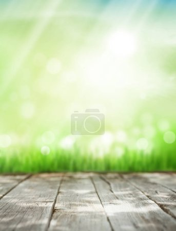 sunny summer background with wooden table and green grass. Toned
