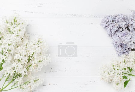 Colorful lilac flowers over wooden background. Top view with space for your text