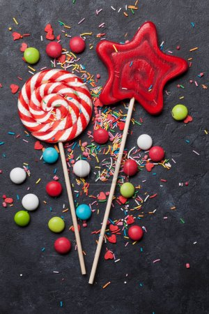 Colorful sweets. Lollipops and candies on dark stone background. Top view