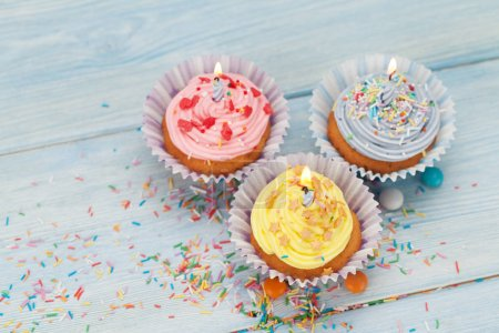 Sweet cupcakes with candles and colorful decor