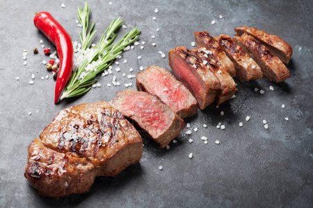 Photo for Grilled sliced beef steak with salt, pepper and rosemary on stone table - Royalty Free Image