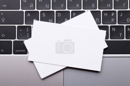 Photo for Blank business cards over laptop keyboard. Top view with space for your text - Royalty Free Image